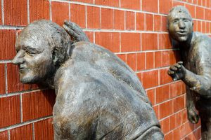 statues listening to a brick wall